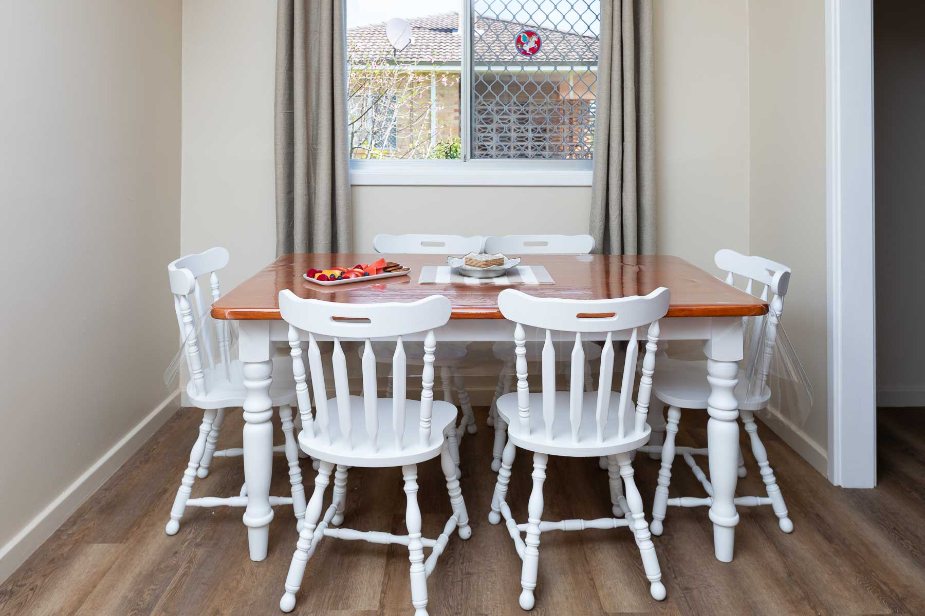 A large table with seating for 6 people is adjacent to the kitchen. There is a dresser stocked with cutlery, crockery and glassware. A reverse cycle air-conditioner cools or heats the living area.
