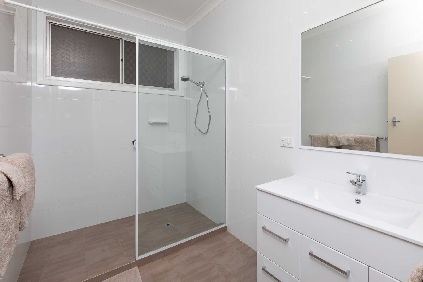 The newly renovated, fully tiled bathroom features a large shower and a vanity basin with mirror. The toilet is separate, and accessed through the laundry.